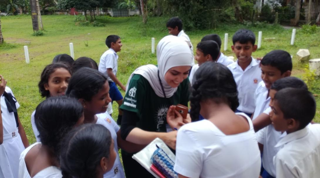 Projects Abroad intern is pictured greeting a group of children at a medical outreach during her nursing internship in Sri Lanka.